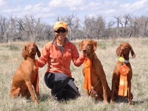 "Mel celebrating Senior Hunter passes with (l to r) ""Kosmo"" - CH Derby's Read Em And Weep MH, ""Remus"" - CH Shakin My Booty Rezzamatazz SH CGC, ""Suede"" - BIR CH Boulder's Power of Persuasion CD RE MH VC ROM."